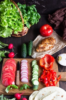 Ingredients for wraps: wheat flour tortillas, roasted chicken, various vegetables, green salad and basil with sauce on wooden board.