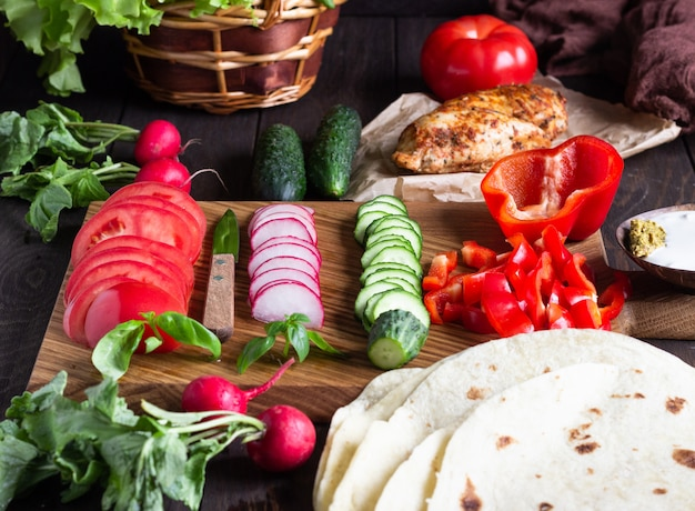 Ingredients for wraps: wheat flour tortillas, roasted chicken, various vegetables, green salad and basil with sauce.