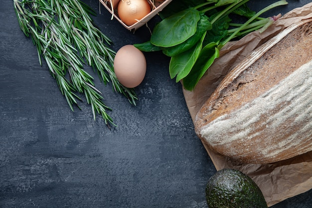 Ingridients for cooking. fresh, organik vegetables, gluten free bread, eco eggs and parsley. spring vegetables, avocado on dark stone background with copy space. flat lay. healthy food concept