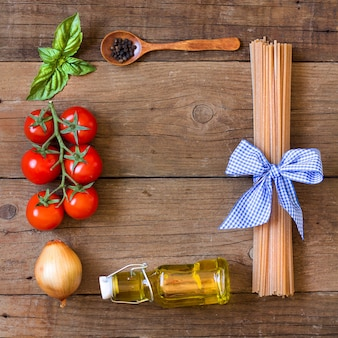 Ingridients for pasta with tomato sauce frame on wooden table top view with copy space