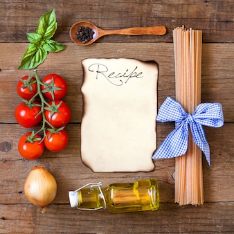 Ingridients for pasta with tomato sauce frame on wooden table top view with paper copy space