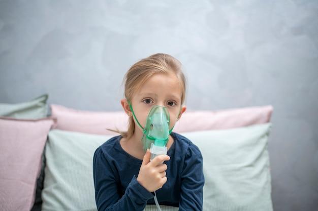 Вдыхание, аэрозоль, 6-летняя девочка делает вдох в спальне у серой стены
