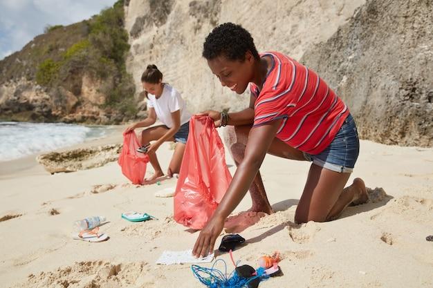 Инициативные девушки смешанной расы собирают мусор с песка