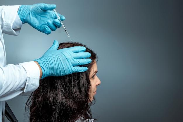 Инъекция для роста волос, руки доктора крупныпы лана делают инъекцию, инъекцию в голову девушки от выпадения волос. здоровье, уход за телом, образ жизни.