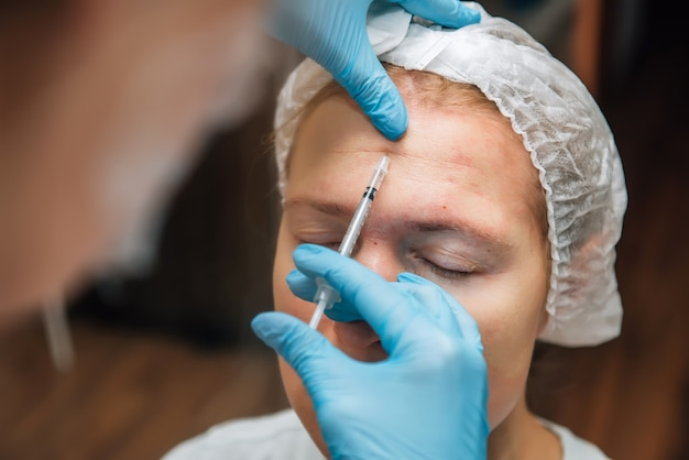 Injection of hyaluronic acid filler under the skin on face of woman