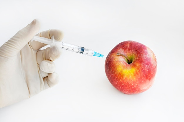 Injection into red apple - genetically modified fruit and syringe with red chemical. gmo food. laboratory research and fruit selection. genetically modified products concept.