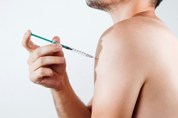 An injection in the shoulder with an insulin syringe