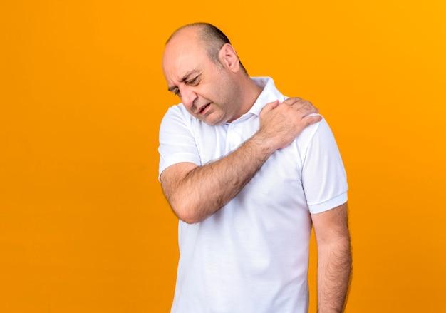 負傷したカジュアルな成熟した男がコピースペースで黄色の背景に分離された肩をつかんだ 無料写真