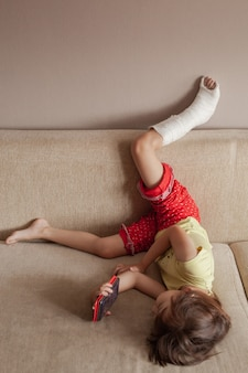 Injured leg of a teenage girl in a cast lying on the sofa at home and playing or watching something in her mobile phone