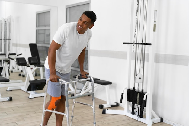 Uomo ferito che fa esercizi di fisioterapia per camminare