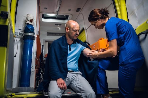 毛布で負傷した男性が救急車で応急処置を受けています