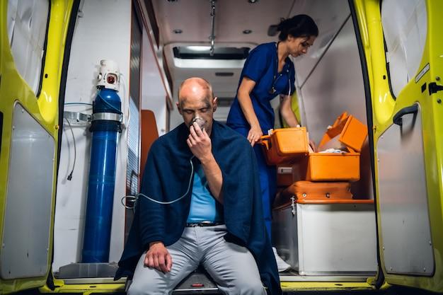 Раненый мужчина сидит с кислородной маской в машине скорой помощи и медсестра, проверяя ее аптечку