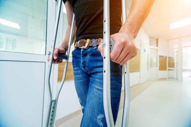 Раненый мужчина пытается ходить на костылях в больнице.