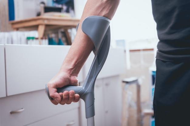 Раненый мужчина пытается ходить на костылях.
