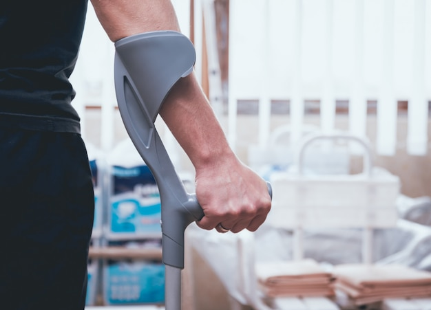 Раненый мужчина пытается ходить на костылях