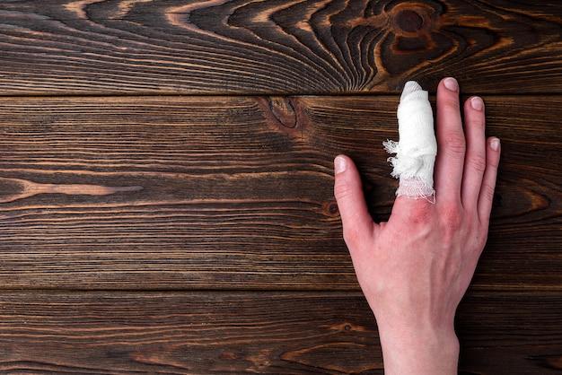 Injured painful finger with white gauze bandage on dark wooden table.