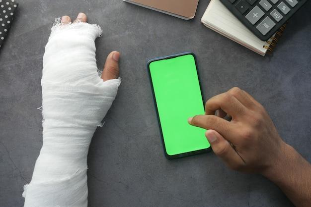 붕대로 고통스러운 손을 다치고 탁자에서 스마트 폰을 사용