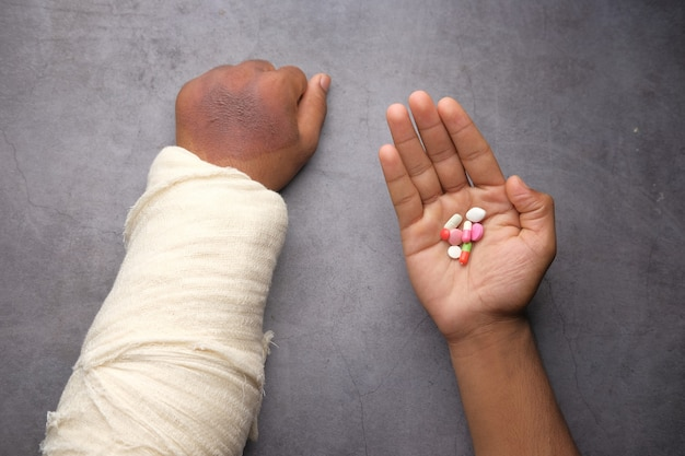 Injured painful hand with bandage and medical pills on hand