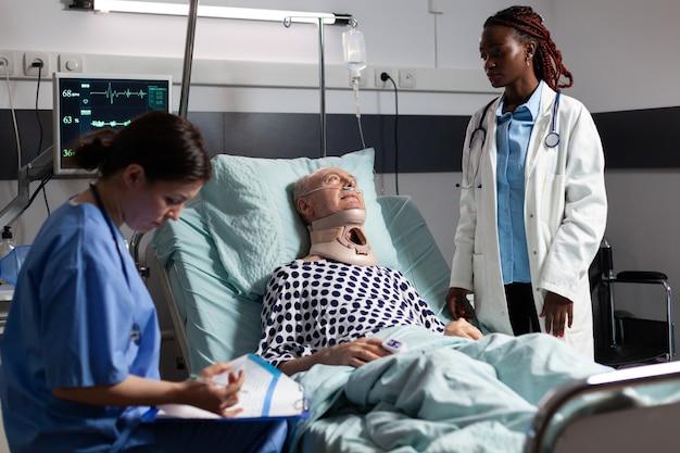 Uomo anziano ferito con tutore per il collo sdraiato a letto che soffre dopo un incidente, discute con il medico durante la visita medica e l'assistente prende appunti negli appunti