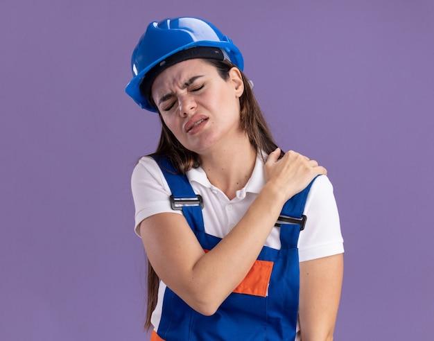 Раненная с закрытыми глазами молодая женщина-строитель в военной форме схватила больное плечо, изолированное на фиолетовой стене