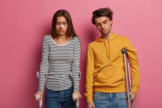 부상당한 여자와 남자가 고립 된 목발로 사고 후 회복