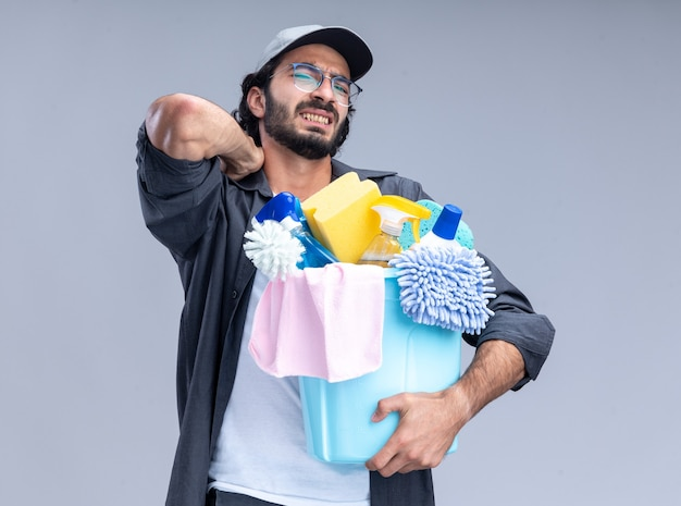 Injured young handsome cleaning guy wearing t-shirt and cap holding bucket of cleaning tools putting hand on aching neck isolated on white wall