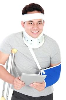 Injured young man using gadget