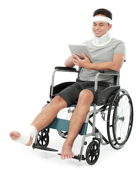Injured young man in wheelchair play gadget