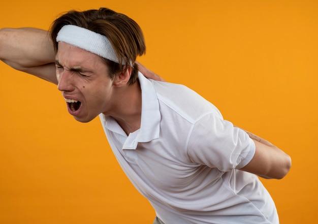 머리띠와 팔찌를 착용하고 부상당한 젊은 스포티 한 남자가 오렌지 벽에 고립 된 아픈 허리를 잡고
