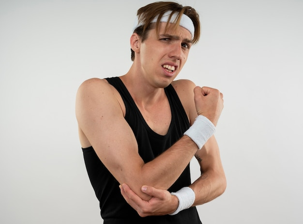Injured young sporty guy wearing headband and wristband grabbed aching elbow isolated on white wall