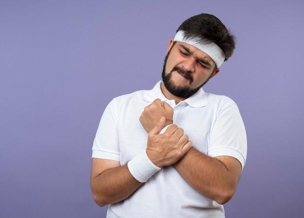 머리띠와 팔찌를 착용하고 부상당한 젊은 스포티 한 남자가 아픈 팔을 잡았습니다.