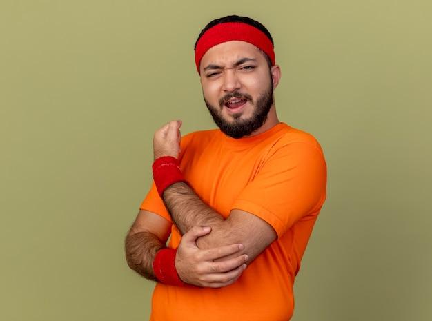 Травмированный молодой спортивный мужчина с повязкой на голову и браслет схватил больной локоть на оливково-зеленом фоне Бесплатные Фотографии