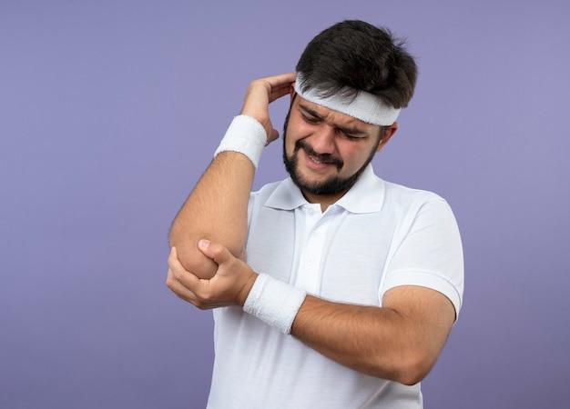 머리띠와 팔찌를 착용하고 부상당한 젊은 스포티 한 남자가 아픈 팔꿈치를 잡았습니다.