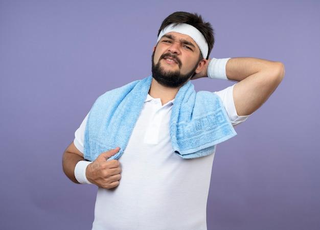 어깨에 수건으로 머리띠와 팔찌를 착용하는 부상당한 젊은 스포티 한 남자가 녹색에 고립 된 아픈 목을 잡고