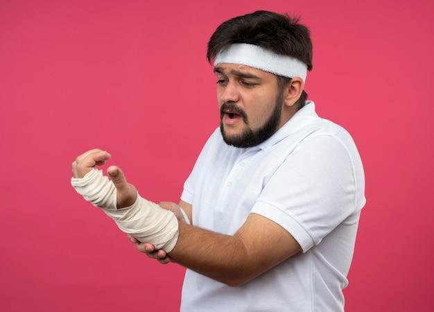 부상당한 젊은 스포티 한 남자가 머리띠와 손목 밴드를 붕대로 감싸고 손목을 잡고 아프다.