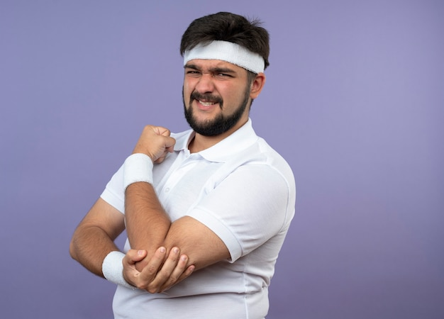 Injured young sporty man wearing headband and wristband grabbed aching elbow isolated on green wall with copy space