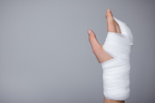 怪我と応急処置の概念-コピースペースで灰色の背景に包帯と石膏で包まれた男性の手
