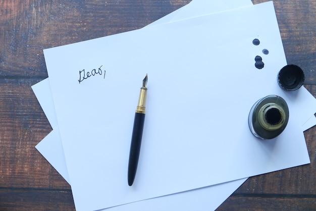 Чернила, пустая бумага и перьевая ручка на столе