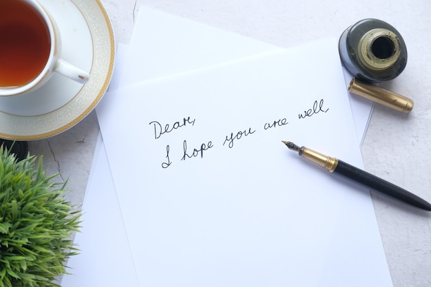 テーブルの上のインクの空の紙と万年筆