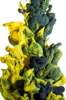 Чернила в воде. всплеск черной и желтой краски. цвет абстрактного фона