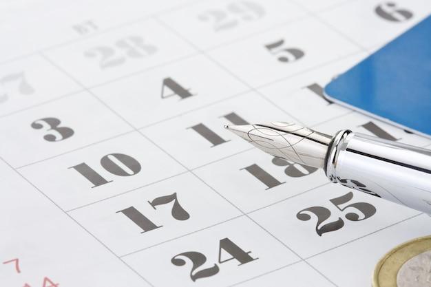 Чернила перо и монеты деньги на календаре