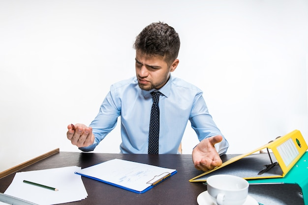 The ink in the pen ended abruptly and the man is forced to write in pencil. young man is absolutly angry and agressed. concept of office worker's troubles, business, advertising, everyday problems.