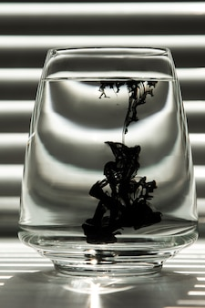 Ink in a transparent glass cup with clear water against the backdrop of a striped screen
