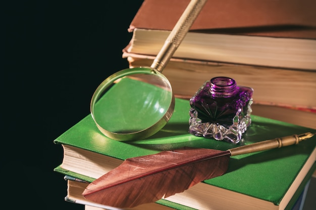 Inkstand with feather near magnifying glass on old books