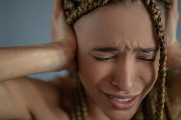 内面の痛み。欲求不満の若いアフリカ系アメリカ人女性が苦しんで、眉をひそめ、手で耳を覆っている