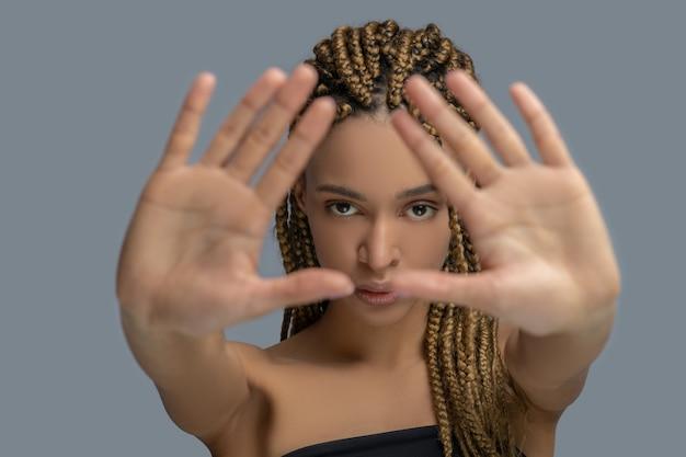 内面の痛み。彼女の手のひらを見せて、自分自身を守ろうとしている悲しい若いアフリカ系アメリカ人の女性