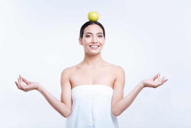 Внутреннее спокойствие. красивая веселая молодая женщина в полотенце медитирует и держит яблоко на голове, позируя у белой стены