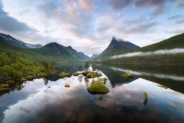 Иннердален - горная долина норвегии. летний пейзаж с озером иннердалсватна и горной вершиной иннердалстарнет. отражение в зеркальной воде