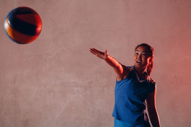Молодой азиатский волейболист женщины в голубом равномерном шарике innings. стандартный волейбольный мяч.