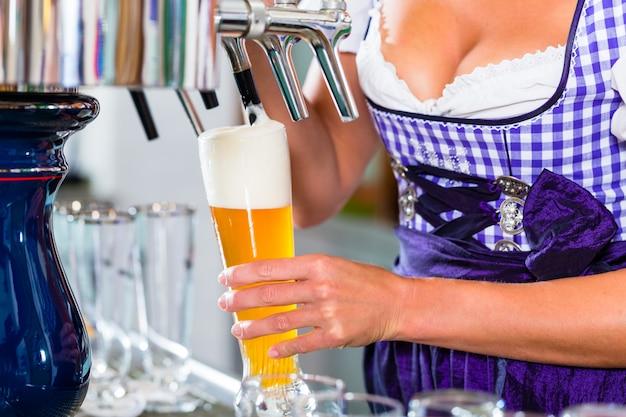 Хозяин гостиницы в баварском пабе рисует пиво